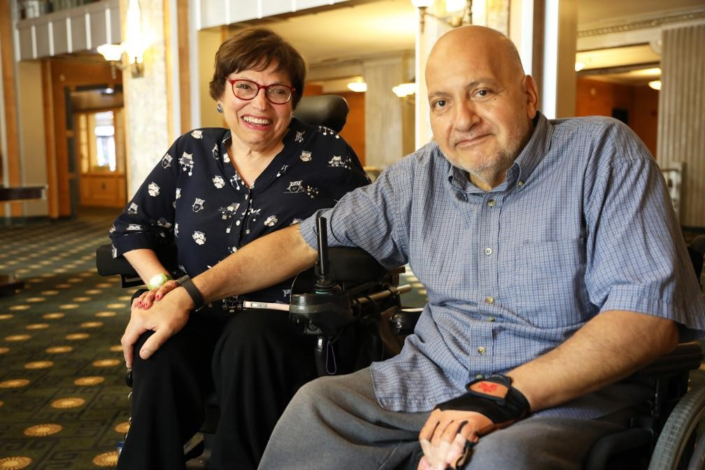 A wholesome picture of Judy and her husband Jorge. Judy is a white disabled women who uses a motorized wheelchair. Jorge is a Mexican disabled man who uses a wheelchair. Jorge is wearing a blue shrit and is holding Judy's hand.