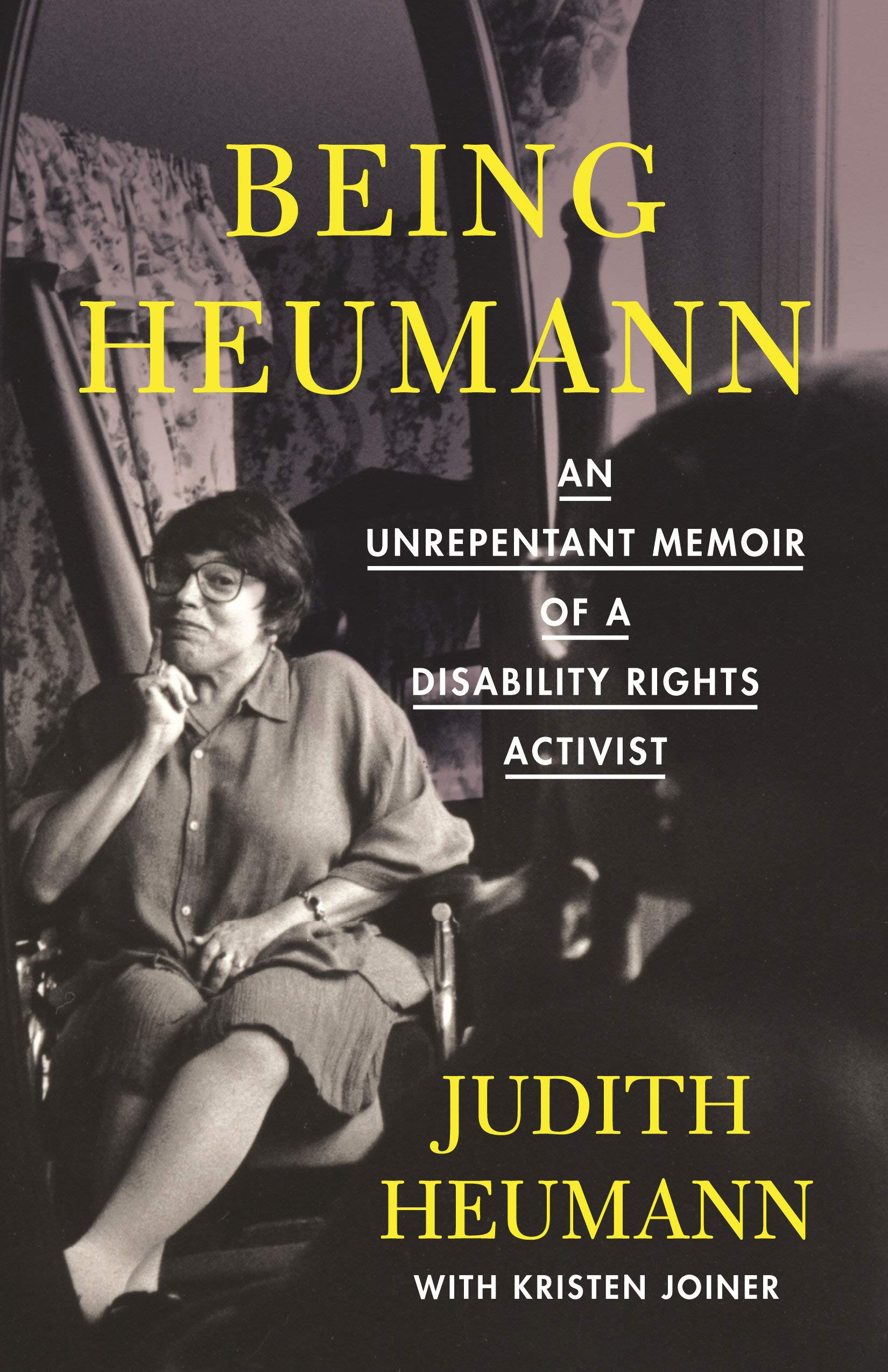 """The cover of the hardcover version """"Being Heumann by Judy Heumann and Kristen Joiner. A black and white picture of Judy with yellow tex reading """"Being Heumann: An Unrepentent Memoir of a Disabillity Rights Activist"""""""