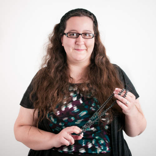 Julia Bascom is a white woman with long dark, curly hair. She is wearing glasses and a black tip. She is holding a stimming toy
