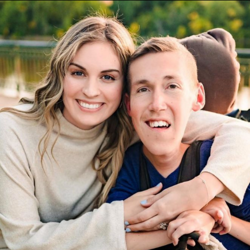 Shane is a white man in his 20s with dark hair streaked with blond. He used a motorized wheelchair. Hannah is a white woman in her 20s with long brown hair streaked with blonde. They are hugging each other and smiling