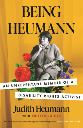 """The cover for the paperback version of """"Being Heumann"""" by judy Heumann and Krsiten Joiner. A black and white picture of Judy surrounded by flowers on a gold background"""