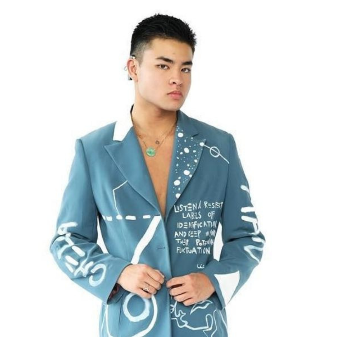 Chella is a genderqueer, transmasculine Asian person in his 20s with thick, black hair. Chella is wearing a blue blazer that he painted with various white abstract designs. He is wearing a cochlear implant