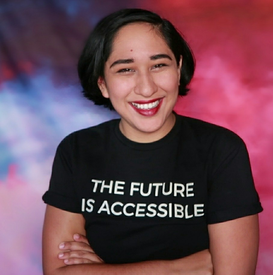 """A headshot of Annie Segarra, a Latinx, genderqueer person with short black hair, wearing a black t-shirt that says """"The Future is Accessible."""" They are against a background that has pink, blue and purple clouds."""