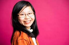A headshot of Wendy Lu, a Chinese-American woman wearing glasses, with straight black hair, and a trach. She is wearing a orange top and pink background