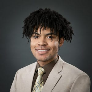 A Black man with short dreadlocks smiling at the camera and wearing a tan colored suit with a matching tie