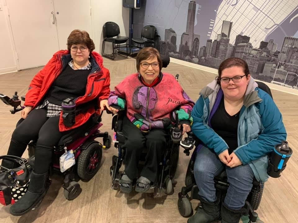 From left to right: Ellen Ladau, a white woman with short brown hair and glasses who uses a motorized wheelchair. Judy Heumann is in the center. Judy is a white disabled woman with short brown hair and uses a motorized wheelchair. On the right is Emily Ladau, a white disabled woman with long brown hair, glasses and uses a motorized wheelchair.