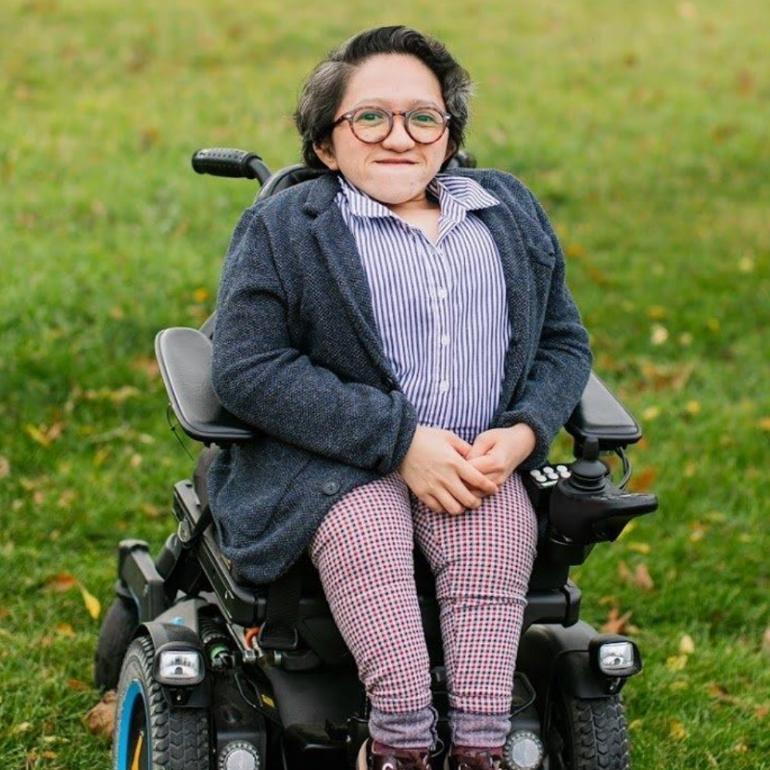 A photo of Sandy Ho. Sandy is an Asian American woman with short black hair. Sandy uses a wheelchair and is in a patch of grass. Sandy is wearing a jacket overtop of a collared shirt with khaki pants and black sneakers