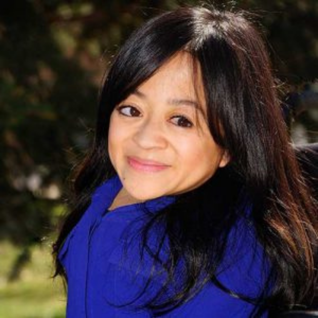 A headshot of Teresa Nyugen. Teresa is an Asian American woman who uses a wheelchair. She has long dark brown wavy hair. She is wearing a royal blue top and is smiling