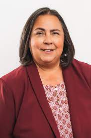 A headshot of Kathy Martinez, who is Latina and has shoulder length brown hair. She is wearing a red blazer with a pink patterned short underneath.