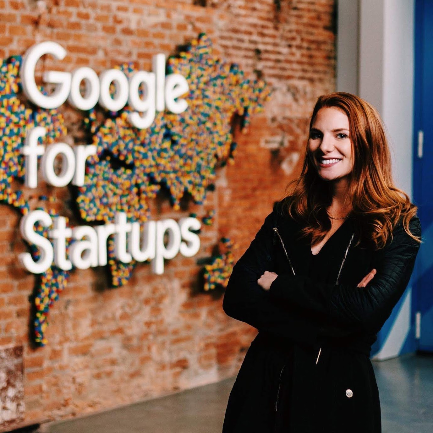 """Photo of Hannah Frankl standing in front of a brick wall with a colorful map of the world and writing that says """"Google for Startups"""". Hannah is a white woman with long read hair wearing a black shirt and jacket. She is smiling and posing with her arms crossed."""